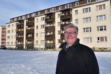 Uwe Hirsch ist in Oelsnitz für 950 Wohnungen verantwortlich. Im Hintergrund die hölzernen Balkone an der Adolf-Damaschke-Straße 51, die in diesem Jahr erneuert werden.