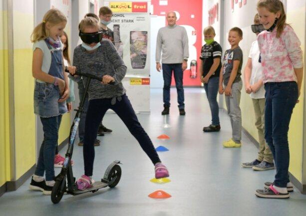 Mit Roller und Alkoholbrille einen Parcours zu fahren, ist nicht einfach. Die Schüler der 5. Klasse an der Oberschule Sayda haben es gemeinsam mit den Zehntklässlern an der Station von Uwe Killisch ausprobiert.