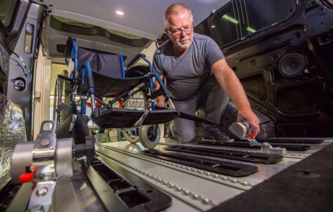 Probestellen: Matthias Schuster testet die Rollstuhlbefestigung in Pauls Auto. Der Fahrzeugboden wurde teilweise durch Aluminium-Planken mit Rasterschienen verstärkt.