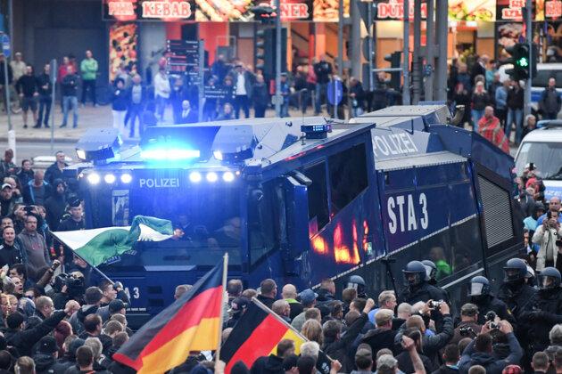 Wasserwerfer bringen sich bei der Demonstration von AfD und dem ausländerfeindlichen Bündnis Pegida, der sich auch die Teilnehmer der Kundgebung der rechtspopulistischen Bürgerbewegung Pro Chemnitz angeschlossen haben,in Stellung. Davor haben Polizisten ihre Wagen zu einer Sperre aufgestellt.