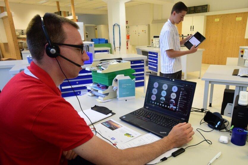Siemens-Trainer Gerry Kebellus schult vom Laptop im Ausbildungszentrum an der Kauffahrtei aus per Videokonferenz Auszubildende, die zu Hause imHomeoffice sind. Hinten - mit Abstand und daher ohne Maske - Auszubildender Felix Rückert mit seinem Firmentablet.