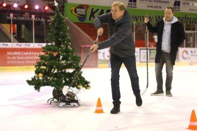 Oberbürgermeister André Raphael schießt eine Weihnachtsbaumkugel auf das Tor. Moderator Mario D. Richardt steht im Hintergrund.