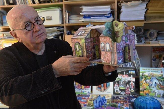 Kurt Völtzke in seinem Atelier in Wittgensdorf bei Chemnitz. Der Reiterhof, den er in den Händen hält, gehört zu seinen Spielwelten aus Pappe.