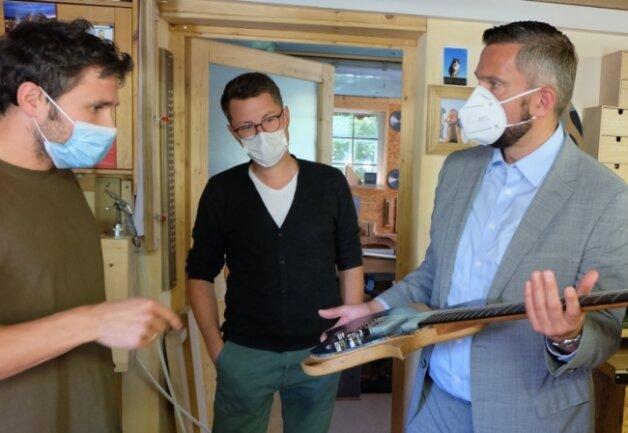 Minister Martin Dulig schaut sich eine E-Gitarre des Modells Gignera an, mit dem Designer Tim Walter und Gitarrenbauer Roy Fankhänel (v.r.n.l.) beim Sächsischen Staatspreis für Design erfolgreich waren.