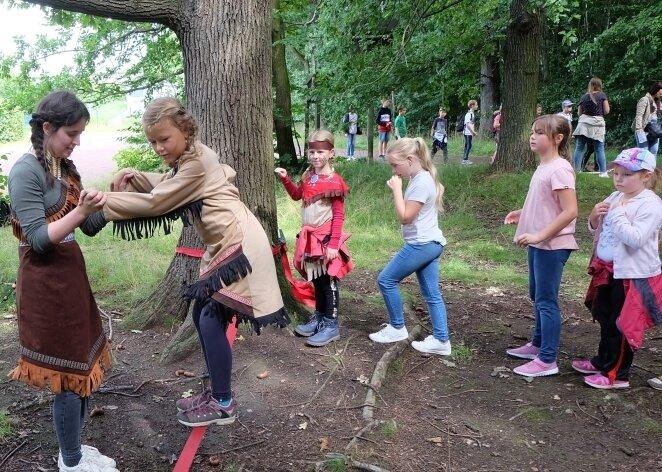 Azubi Vanessa Tennert (links) hilft der siebenjährigen Anna beim Überwinden der Slackline, bei der die Kinder ihre Geschicklichkeit bewiesen haben.