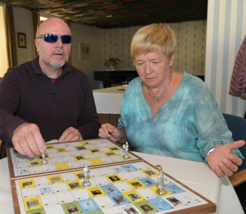 Reiner Groneberg und Gabriela Blechschmidt, die Schatzmeisterin im Verein Blinder und Sehbehinderter Aue-Schwarzenberg, am vorgestellten Brettspiel.
