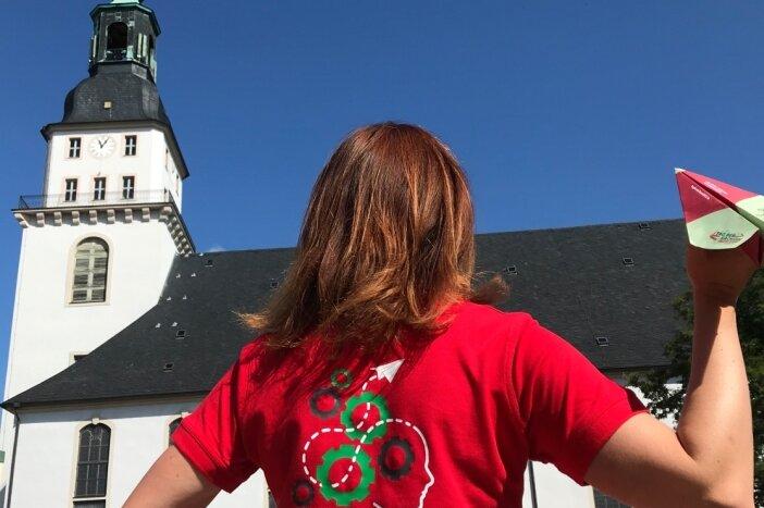 Der Tag der Sachsen 2022 ist im Anflug auf Frankenberg. Für das Logo stand die Schlangenbrücke Modell und schlängelt sich nun durch dieses hindurch. Das Bauwerk verbindet den für die Landesgartenschau geschaffenen Naturerlebnisraum Zschopauaue mit der Altstadt und steht zugleich für den Pioniergeist der Stadt.