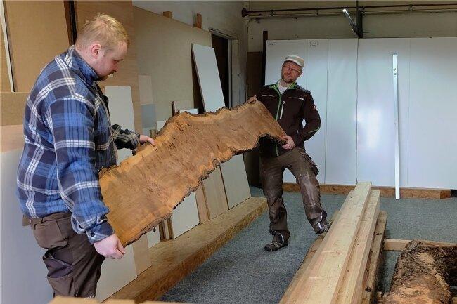 Dieses als Rüster-Maser bezeichnete Ulmenholz, welches Heiko Kretzschmar (rechts) für einen Tisch braucht, ist im Handel erhältlich. Doch die Materialbeschaffung wird für den Brünloser Tischlermeister und Restaurator (im Bildmit seinem Gesellen Yannic Grießbach) zunehmend ein Problem.