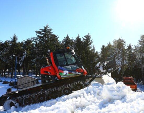 Am Anfang wird der Schnee mit Lkw antransportiert, danach mit dem Pistenbully zu einem Berg aufgeschoben.