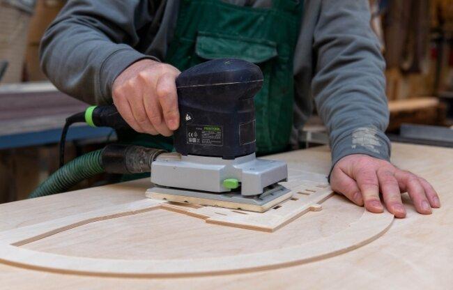 Mit der Schleifmaschine werden die verschiedenen Teile der künftigen Fensterbilder geglättet.