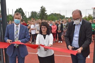 Der Lichtenauer Bürgermeister Andreas Graf, Schulleiterin Kerstin Wilde und Kultusminister Christian Piwarz (von links) vollzogen den symbolischen Schnitt zur Freigabe der Sportfläche.
