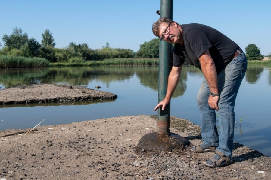 Volker Fuhrmann von den Teichwirtschaften Fuhrmann und Schlegel aus Schweikershain zeigt auf den niedrigen Wasserstand am Vorstau in Schwarzbach. Mehr als ein halber Meter fehlt dort.