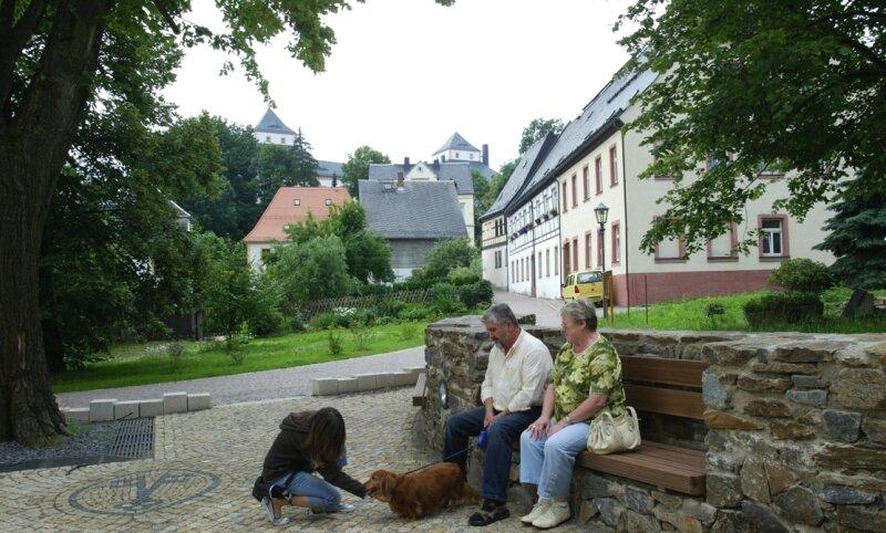 Familie Ehle aus Zella-Mehlis in Thüringen mit Enkeltochter und Dackel fühlen sich wohl auf der nicht unumstrittenen neu gestalteten Bank in der Natursteinmauer am Augustusburger Kirchplatz.