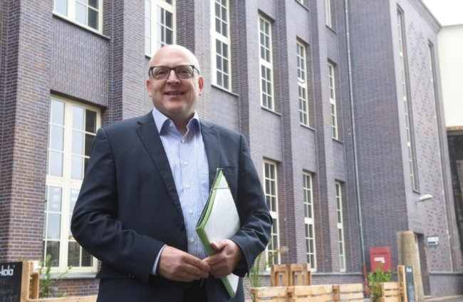 Sven Schulze - wie man ihn kennt, den Zahlenmenschen. Ob in der Mappe die neuesten Chemnitzer Haushalt-Eckpunkte stehen? Zuletzt musste die Stadt auf Gewerbesteuereinnahmen verzichten. Um so wichtiger sind wohl junge Unternehmen, die sich in der Stadt ansiedeln. Ein Beispiel dafür ist das ehemalige Wirkbau-Gelände im Hintergrund.