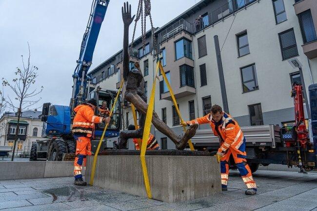 """Mitarbeiter des Hoch- und Tiefbau Reichenbach, vorn Steffen Holzmüller und Klaus Schädlich (r.), lassen den auf einem Betonquader befestigten """"Jahrhundertschritt"""" in die Fundamentgrube ein."""