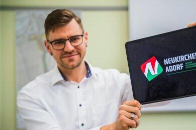 Bürgermeister Sascha Thamm zeigt das neue Logo. es soll sowohl ein N für Neukirchen darstellen, als auch ein A für Adorf.