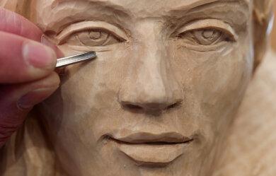 Ein Schnitzer arbeitet bei den erzgebirgischen Schnitzertagen an einem Frauenporträt.
