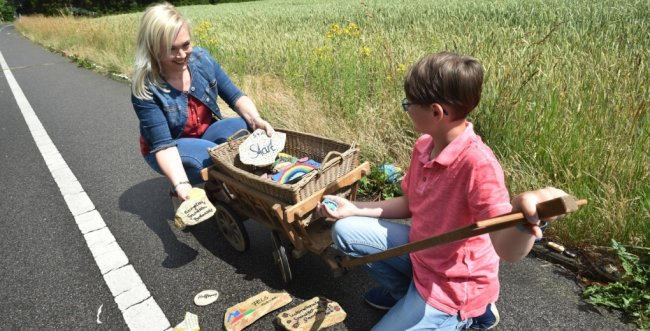 Steinschlange-Initiatorin Anja Ulbrich und ihr Sohn Benjamin legen einige Teile des Kunstwerkes an der Rußdorfer Straße in einen Bollerwagen. Die Familie will sie vorerst zu Hause aufbewahren und dann zum neuen Spielplatz an der Frohnbachstraße bringen.