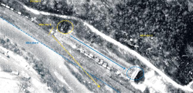 Ein bekanntes Bild neu interpretiert. Zu sehen sind der Poppenwald (oben), die Talstraße und die EisenbahnlinieZwickau - Aue, nahe dem Bahnhof Niederschlema. Das Vorhandensein zweier Gebäude (gelber und blauer Kreis) und mehrerer Züge ist unumstritten. Neu ist die Interpretation der dunklen Fläche in der Zwickauer Mulde als verkippter Abraum. Die gepunktete blaue Linie ist die Uferlinie der Mulde. Die Gebilde neben der Freifläche (blauer Pfeil) galten bisher als Waggons, sie könnten auch gestapelte Kisten und Container sein.