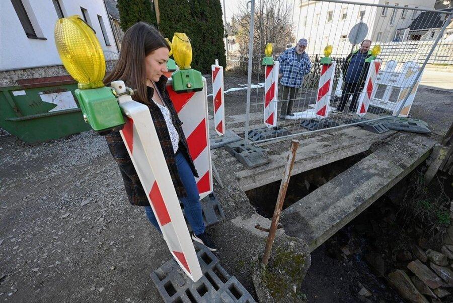 Anwohnerin Sindy König schaut auf die marode Brücke an der Hauptstraße in Taura, die jetzt abgerissen werden soll. Sie und weitere Grundstücksbesitzer wie Joachim Heinze und Mike Eichhorn (rechts) fordern einen Neubau. Doch das ist bisher nicht geplant.