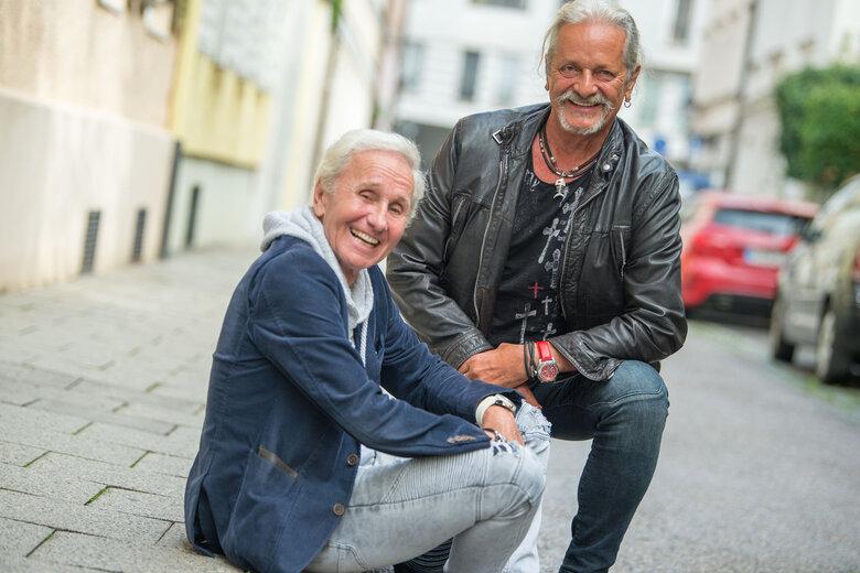 Klaus Eberhartinger (l.), Sänger bei der Ersten Allgemeinen Verunsicherung (EAV), und Thomas Spitzer, Gitarrist und Texter bei EAV, sitzen bei einem Interviewtermin mit dpa auf einem Bürgersteig. Die EAV hört nach über 40 Jahren auf und verabschiedet sich entgegen ihrem humoristischen Ruf mit einem sehr politischen Album.