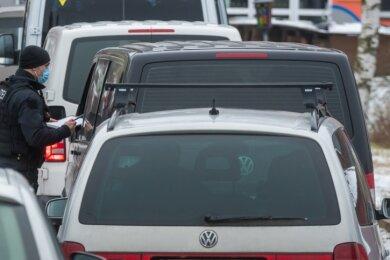Polizisten kontrollieren auf dem Parkplatz an der Sommerrodelbahn in Seiffen Autos mit auswärtigen Kennzeichen. Von 13.30 bis 17.15 Uhr registrieren die Beamten 34 Verstöße gegen die geltenden Corona-Regeln.