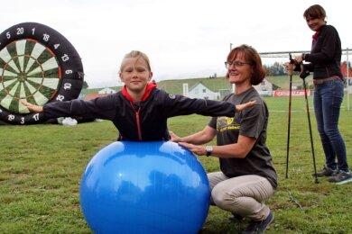 Fenja (l.) ließ sich beim Fest des SV Fortschritt Lunzenau von Kerstin Sachse-Sterlemann (M.), Abteilungsleiterin Reha-Sport, Übungen mit dem Gymnastikball zeigen. Janett Dohl (r.) bietet beim Verein Nordic-Walking-Training an.