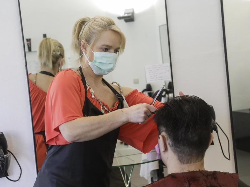 Wenn Friseure ihre Salons wieder öffnen, müssen sie und ihre Kunden einen Mundschutz tragen.