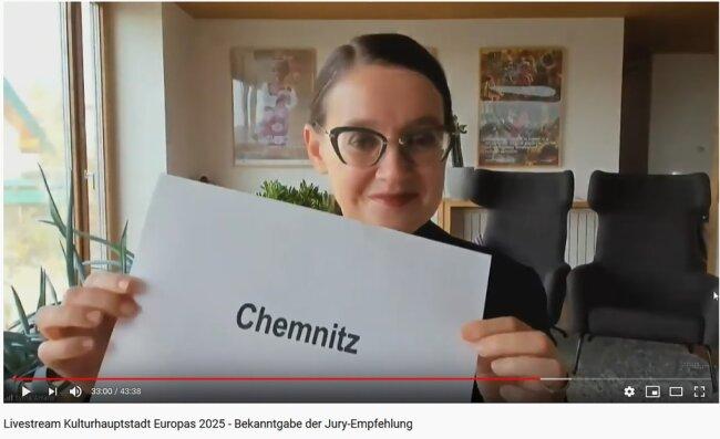 And the winner is ... Jury-Vorsitzende Sylvia Amann hält im Livestream den Namen der Gewinnerstadt in die Kamera: Chemnitz!