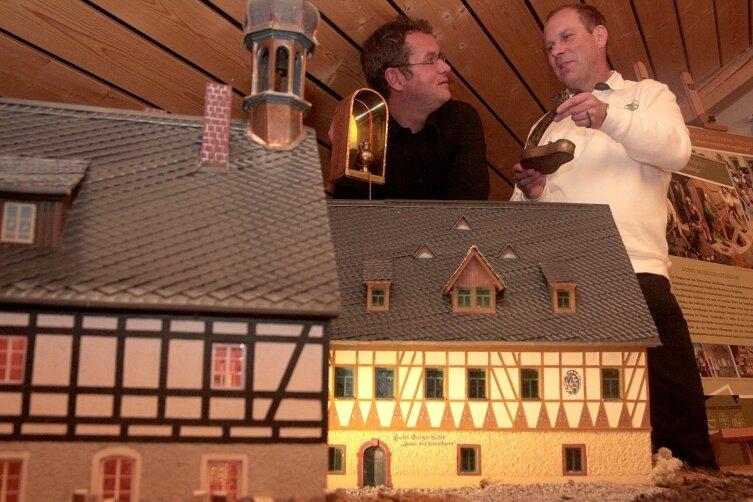 """<p class=""""artikelinhalt"""">Knut Liebscher (links) und der Leiter des Museums Pferdegöpel, Wolfgang Fritzsche, mit historischem Geleucht hinter dem Modell der Saigerhütte. </p>"""