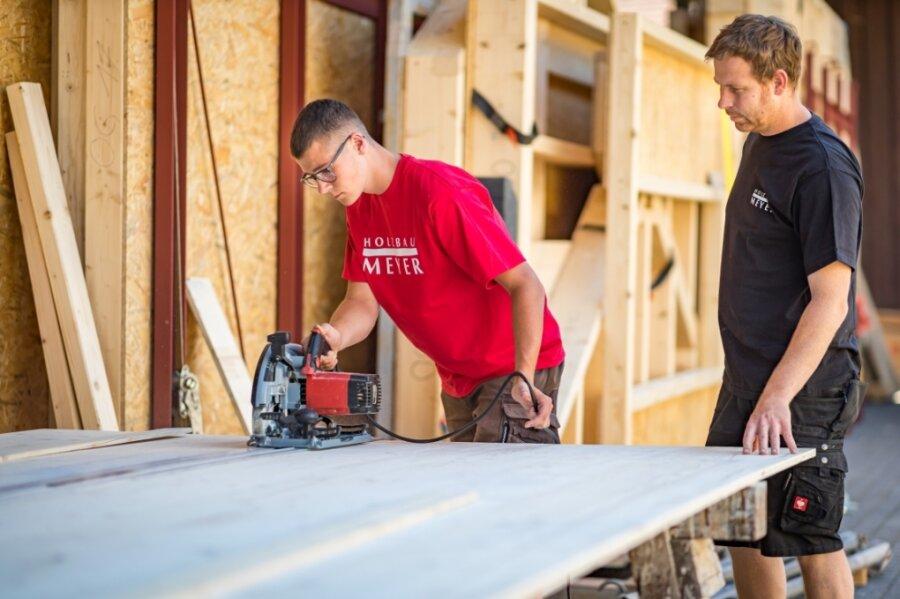 Moritz Hauser (links), Azubi bei Holzbau Meyer in Stollberg, schneidet eine Holzplatte zurecht. Geschäftsführer Simon Meyer leitet ihn an. Angesichts des Fachkräftemangels setzt der Unternehmer auf Ausbildung.