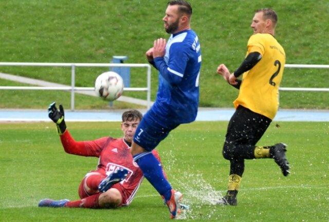 Schwierige Bedingungen: Auch Routinier Roy Blankenburg (M.), hier gegen Rabenstein Torwart Markus Landgraf, hatte mit dem durchweichten Rasen stark zu kämpfen.