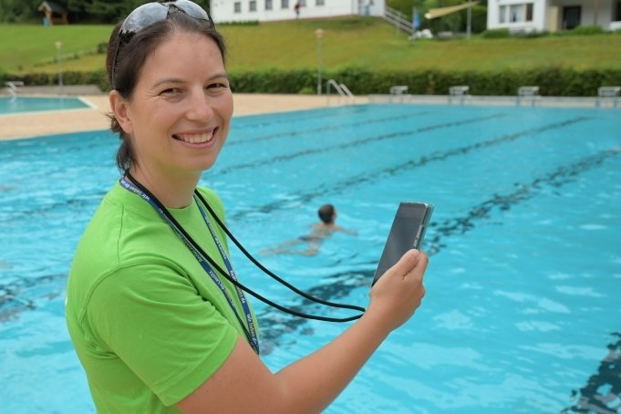 Anne Arnold steht mit der Stoppuhr auf den Handy am Beckenrand und misst die erworbene Ausdauer von Grundschülern beim Schwimmen.