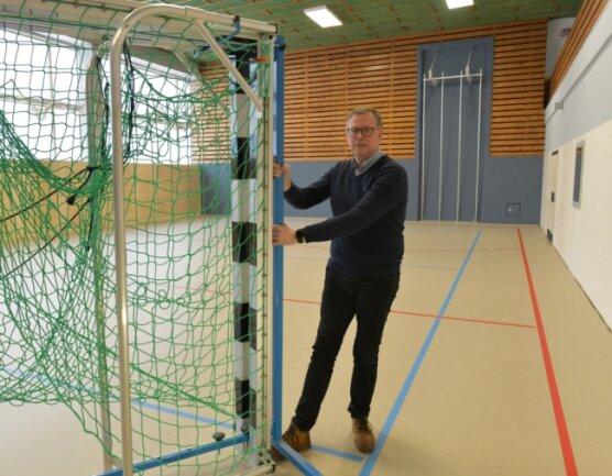 Bürgermeister Rico Gerhardt (CDU) rückt in der Schulturnhalle in Oberschöna schon einmal die Geräte zurecht. Hier wurden unter anderem das Parkett gegen einen Sportboden getauscht und Prallwände montiert.