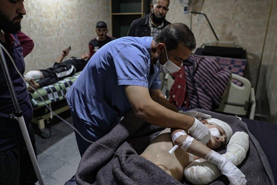 Ein Sanitäter versorgt ein Kind, das in der syrischen Stadt Ariha bei einem Raketenbeschuss verletzt wurde.
