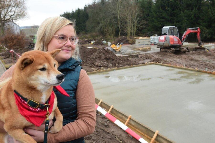 Nicole Schreiter mit ihrem Shiba-Inu-Rüden Kouki vor der Baustelle für ihr Eigenheim in Niederlichtenau. Die Tierärztin will sich in der Gemeinde Lichtenau mit einer Tierpraxis niederlassen, setzt aber auch auf die Beratung via Internet.