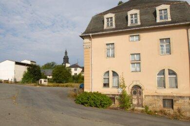 Das Herrenhaus (rechts) soll laut Käufern erhalten und saniert werden. Auf den Flächen hinter dem Bauzaun sind Einfamilienhäuser vorgesehen.