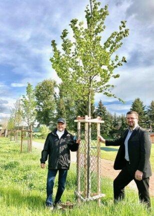 Bürgermeister Siegfried Baumann (links) und Markus Teubner freuen sich über die jungen Laubbäume auf dem Schulareal.