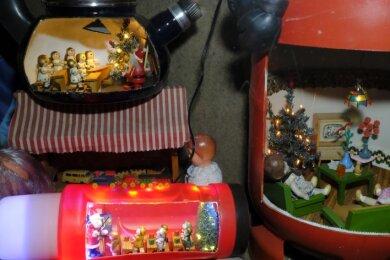 Neu im Schaufenster an der Feldstraße: Miniatur-Weihnachtsschulen in einem DDR-Teekessel und einer DDR-Thermosflasche. Am Abend kommt die beleuchtete Szenerie besonders schön zur Geltung. Rechts eine bereits vor drei Jahren in eine Propangasflasche drapierte Puppenstube.