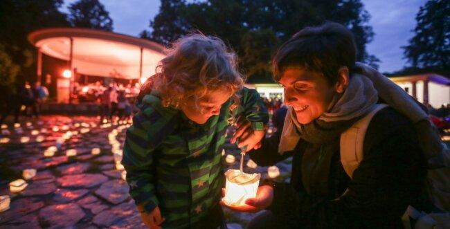 Nach Auftritten mehrerer Künstler auf der Schloßteichinsel wurde mit Hilfe der Gäste das sogenannte Lichterlabyrinth entzündet. Dazu verteilten auch die Besucher - im Bild: Paulin (3) mit ihrer Mutter Sandra Großmann - insgesamt 1000 Lichter auf dem Platz vor dem Pavillon.