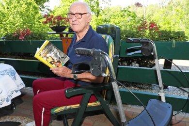Siegfried Walther in seinem Gartenstuhl mit einem Buch über Dynamo Dresden.