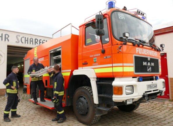 Wehrleiter Jens Fichtner (M.) gibt eine Einweisung am Tanklöschfahrzeug, das die Scharfensteiner aus der Partnerstadt Eichenau ausgeliehen haben. Sobald das neue TLF da ist, wird es zurückgebracht.