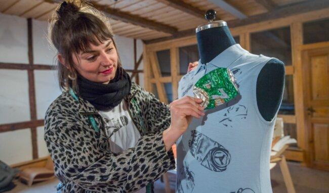 Franziska Heinze aus Schneeberg stellt Upcycling-Kleidung her. Im Bild zeigt sie eine der gesammelten Dosen, die auf T-Shirts gedruckt werden.