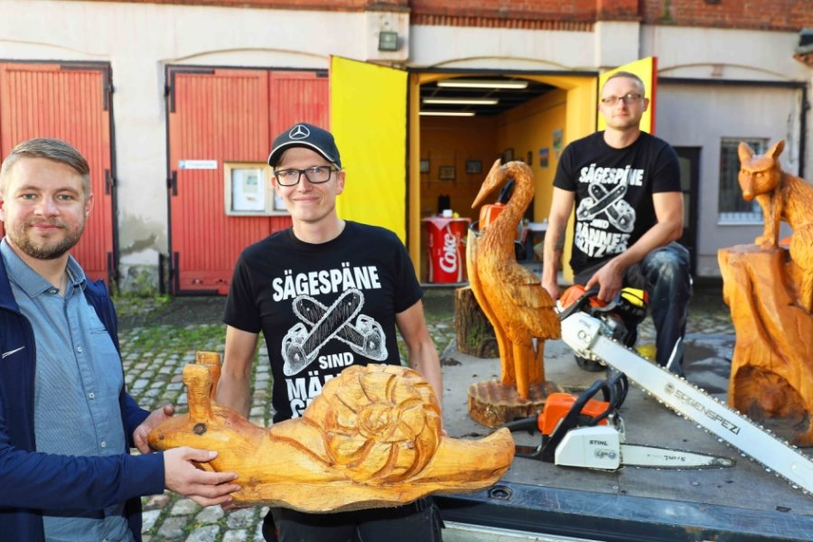 Thomas Sprotte, Vorsitzender des Jugendclub-Fördervereins, mit den Kettensägen-Hobbykünstlern Jean-Philipp Russel und Michael Germuhl. Ihre Werke, meist Tierfiguren, sind zwischen 30 Zentimeter und zwei Meter groß.