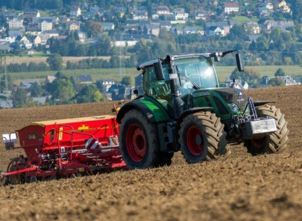 Ein Olbernhauer Landwirtschaftsbetrieb sät mit Traktor und angehängter Drillmaschine Getreide aus.