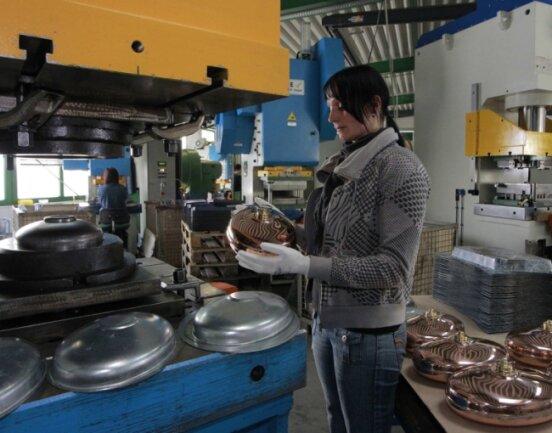 """<p class=""""artikelinhalt"""">Manuela Hartmann beim Tiefziehen von Wärmflaschen-Oberteilen. Die Behälter gibt es aus Zink und Kupfer.</p>"""
