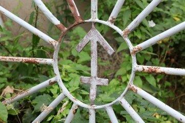 Markenzeichen des Pfeilhammers als Symbol am Tor eines Nebenzugangs.