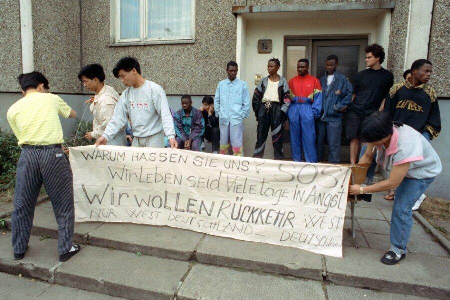 """""""Warum hassen sie uns? SOS!"""" steht auf dem Transparent, das Asylbewerber vor ihrer Unterkunft aufstellen."""