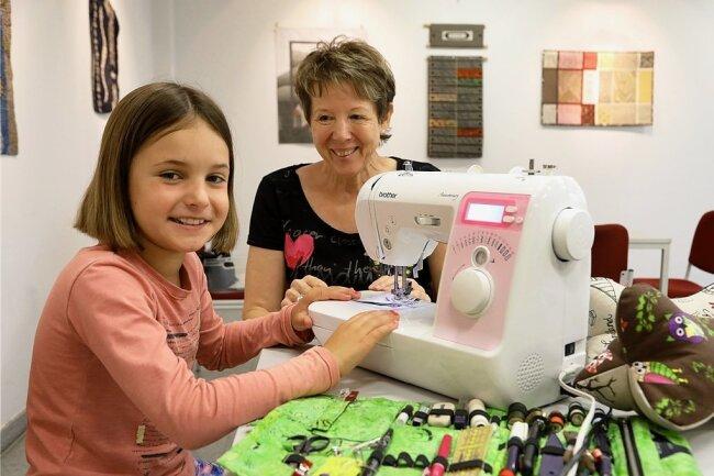 """An diesem speziell für Kinder angefertigten Gerät lernt die neunjährige Johanna am Donnerstag das Nähen. Zwar ist sie die einzige Teilnehmerin des Kurses """"Leseknochen herstellen"""" im Hohenstein-Ernstthaler Textil- und Rennsportmuseum (TRM). Johannas Gesichtsausdruck nach zu urteilen, scheint das dem Spaß aber keinen Abbruch zu tun. Die """"Museumswerkstatt"""" gibt es seit vielen Jahren. Wie zuvor, stand auch dieses Jahr wieder Evi Mühlstedt (Foto) den Kindern mit ihrem Rat und geschickten Händen zur Seite. Bei den Leseknochen handelt es sich übrigens um eine Art Nackenkissen, das, wie der Name schon sagt, etwa eine gemütliche Lesehaltung auf der Couch ermöglicht. Das Ferienprogramm des TRM fand an zwei Tagen statt und ist für Schüler und Schülerinnen ab der ersten Klasse gedacht. Neben Leseknochen konnten die Kinder auch unter Anleitung Jeansmäppchen oder bunte Tierkissen herstellen.akli"""