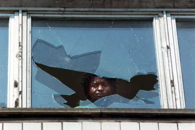 Ein Mann blickt am Tag nach den ausländerfeindlichen Übergriffen durch die eingeworfene Scheibe eines Wohnheims.